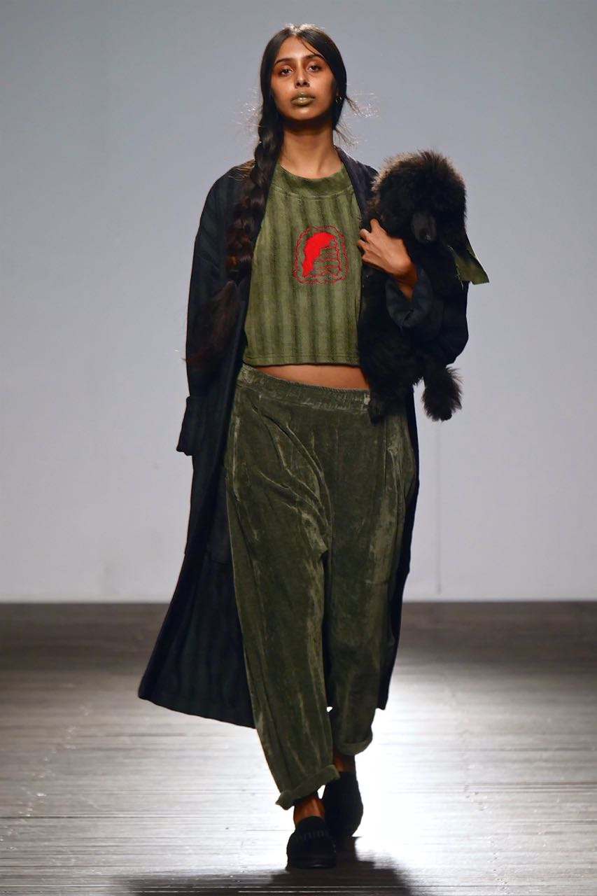 Tyra Naidoo walking in a dark green outfit at a fashion show