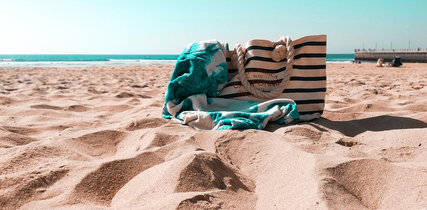 a beach towel lying next to a bag on beach sand