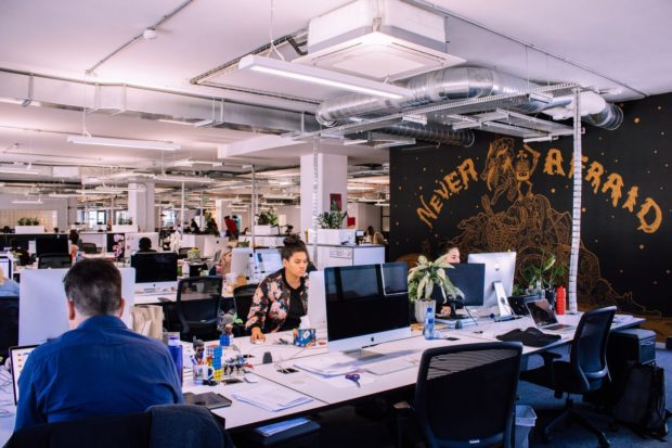 "a creative office in cape town with staff sitting at their desks working on macs, on the right is a black wall with ""never afraid"" written on it"