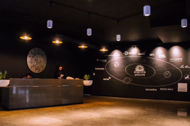 Two secretaries are at their desks in an office entrance in Cape Town with a solar system image with the companies in the building