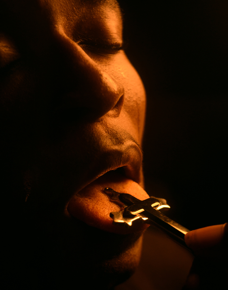 a person holding a gold cross on their tongue taken by adeolu asibodu