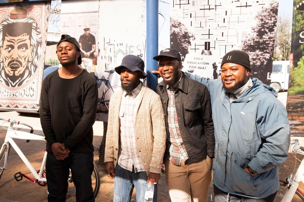 the four founders of bicycle stokvel standing in front of art murals