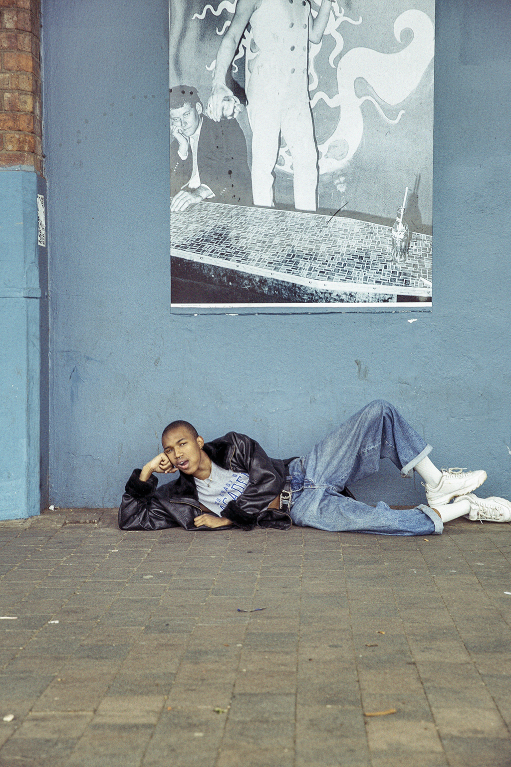 a man lying on the floor in front of a blue wall
