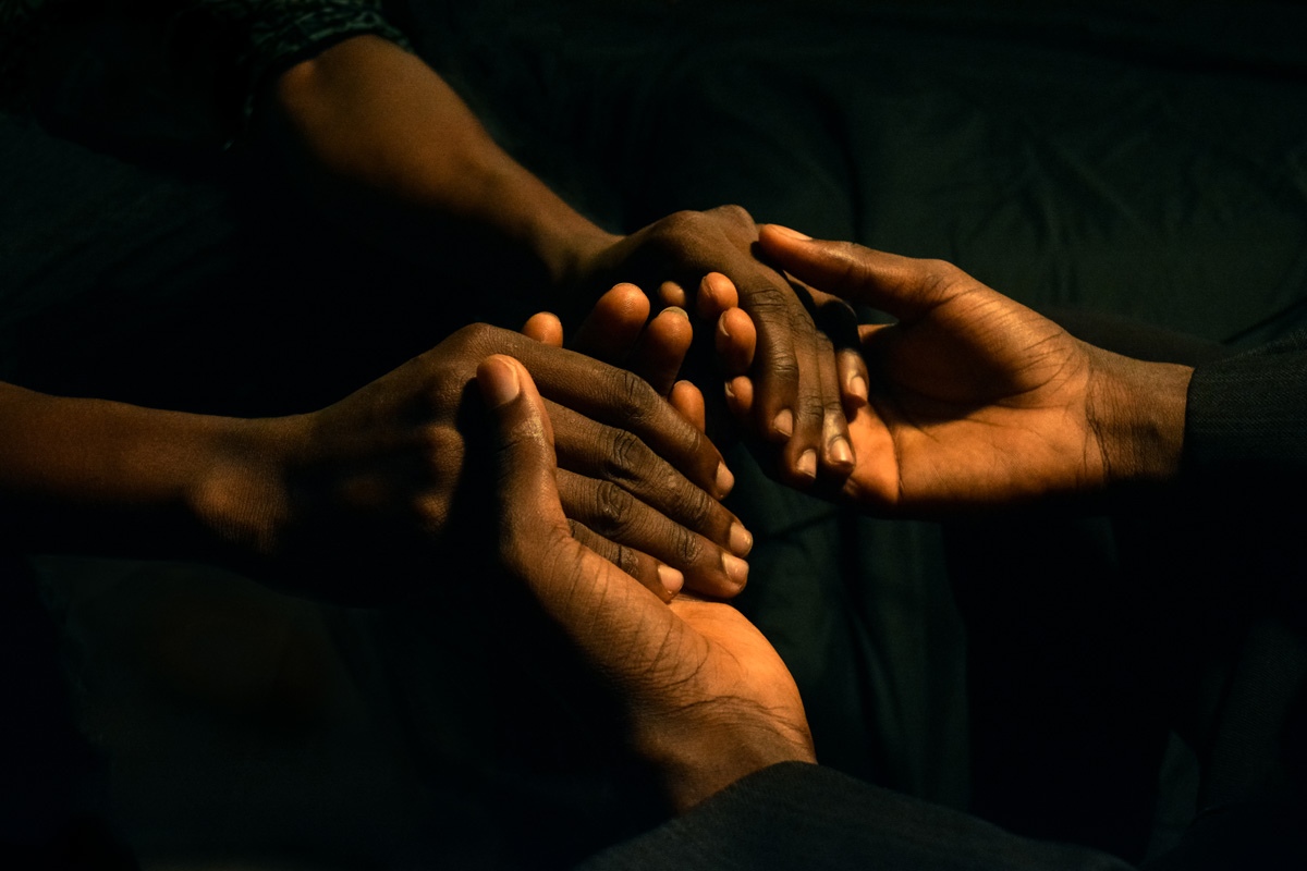 two sets of hands holding each other in prayer