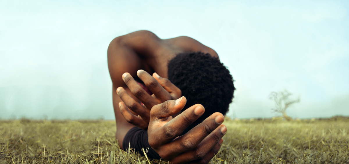 a man lying in grass with his head on his arms