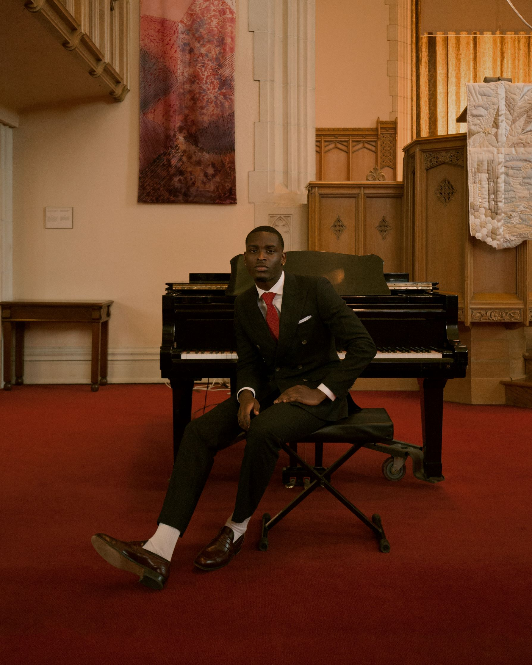 Josef Adamu sitting in front of a piano in a church