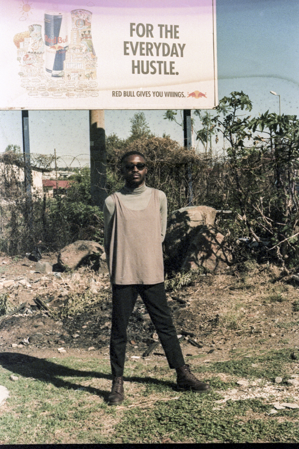 a man standing in front of a billboard in soweto for Sipho Gongxeka photo series