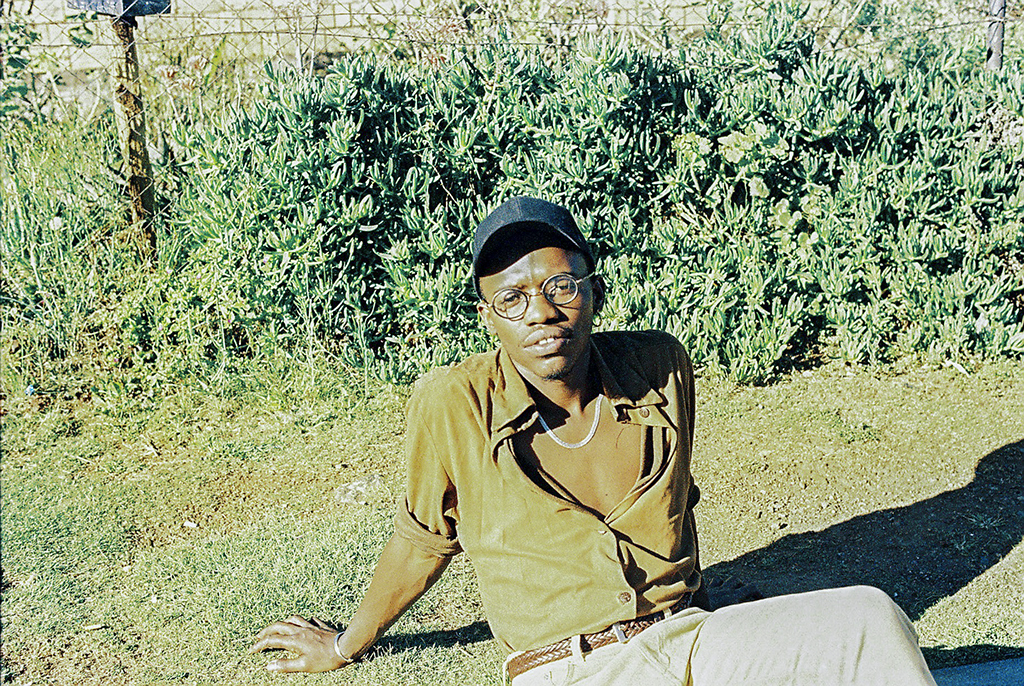a man sitting on grass with a hat and glasses on