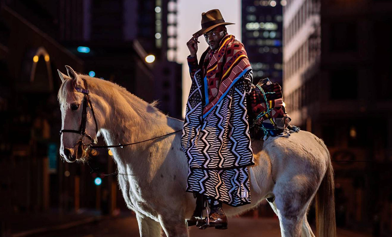 A man on a horse in the city wearing a Laduma Ngxokolo designed blanket