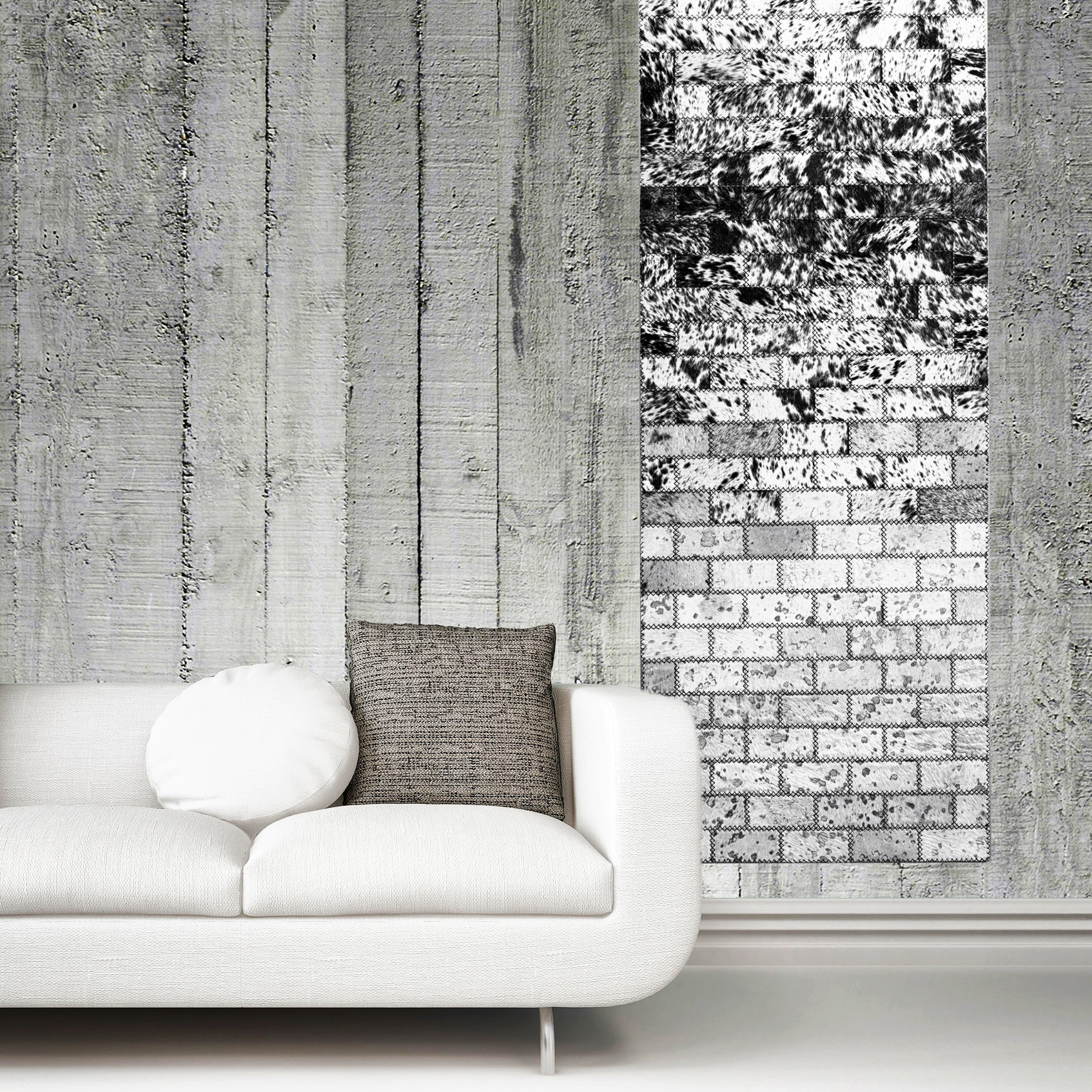 Greyscale image of an upholstered white sofa against a concrete wall over a plain white floor with skirting board