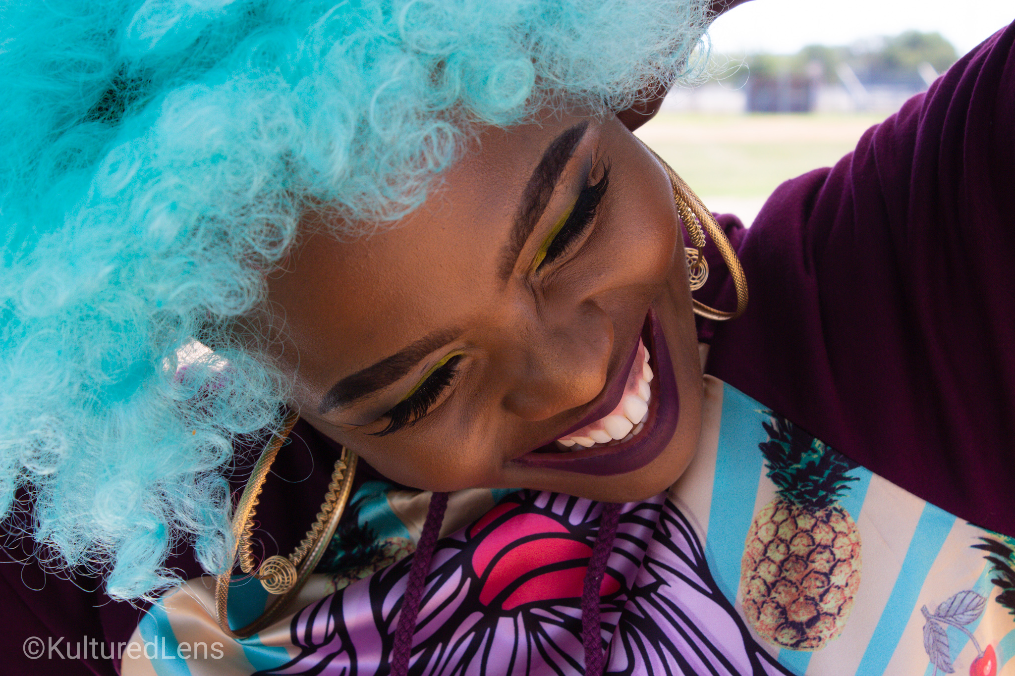 Portrait of a woman with blue hair smiling by Kultured Lens