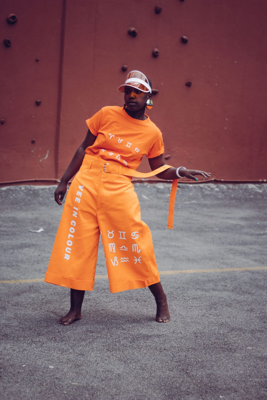 A lady in an orange Vee in Colour outfit.
