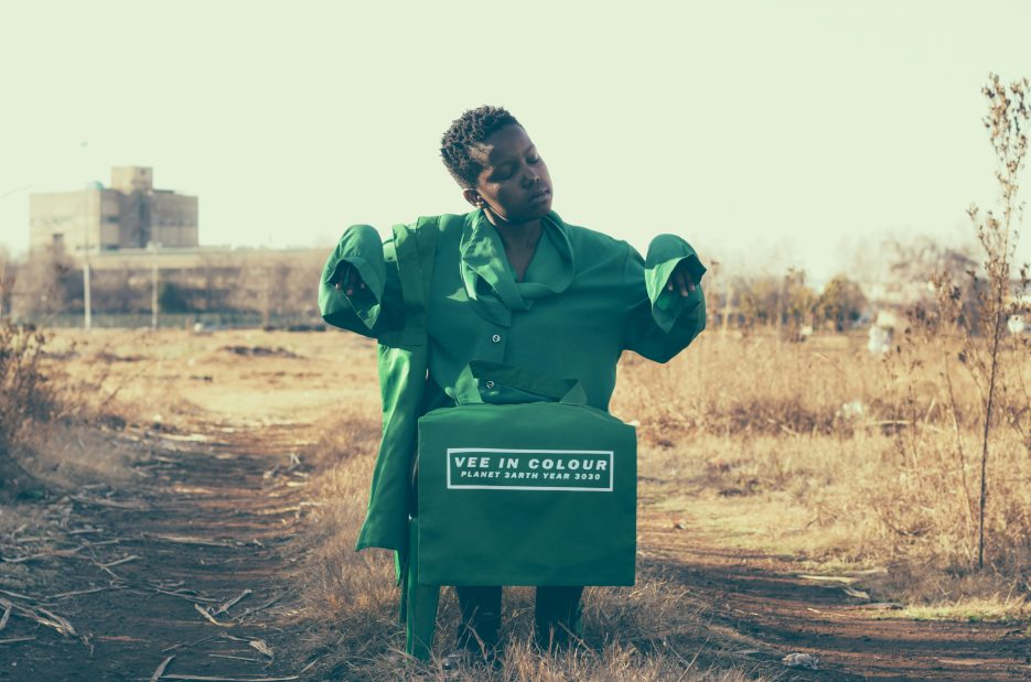 A young boy wearing an oversized green Vee in Colour shirt with a box in front of him.