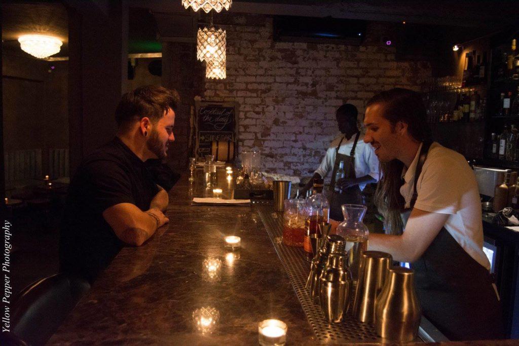 A bar tender serving a drink at Sin Tax Bar